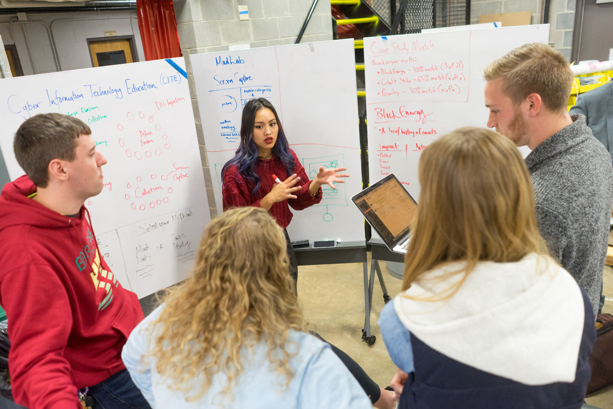 A student leads a brainstorming session with her team