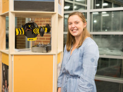 Students stands beside drone prototype to save bees.