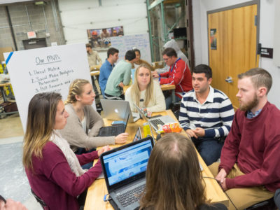 A student team sits around a table working on their client's problem