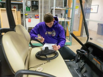 A student works on the detached steering wheel of the golf cart.
