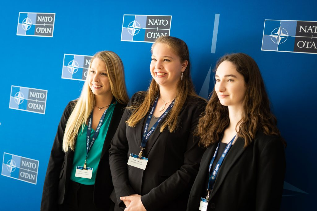 Team stands in front of NATO step and repeat banner.
