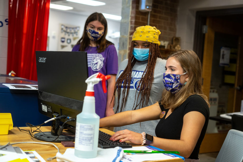 Masked students program the laser cutter