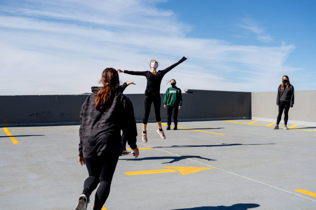 Students perform a dance on a parking garage rooftop
