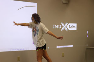 Masked student swipes her hand across a wall, which uses technology to draw a virtual line across it