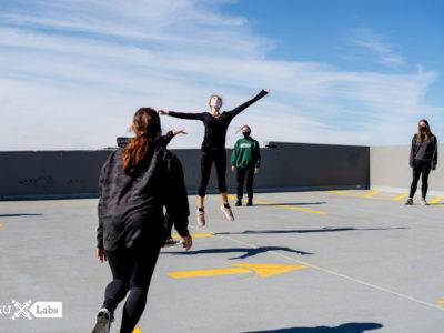 Masked students in black dance on the rooftop of a parking garage