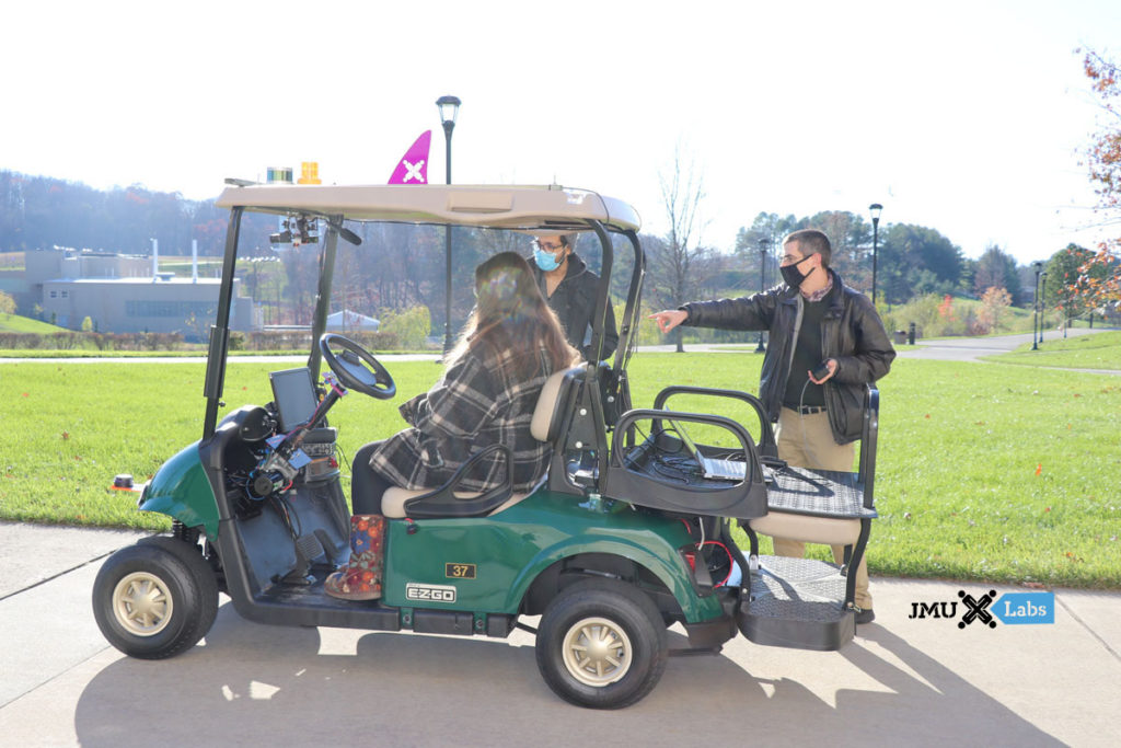 A reporter rides in the autonomous golf cart