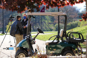 A reporter interviews Professor Sprague in front of the golf cart