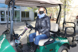 A woman sits in the autonomous cart while a reporter interviews the professor