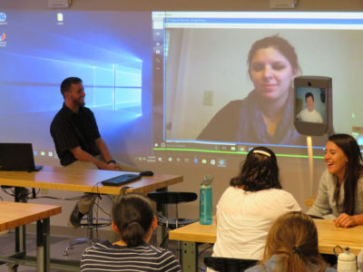 A class talks with people on a Beam robot and through telepresence.