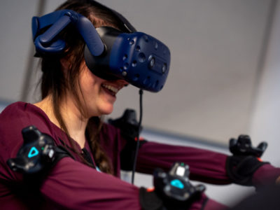 A girl wearing a VR headset and sensors smiling